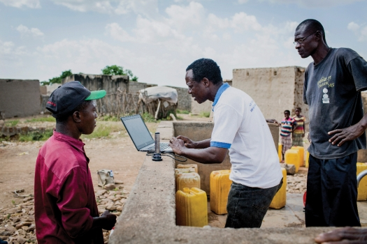 An official checks data from an internet-based water monitoring device at a borehole in Basbedo, Burkina Faso. Photo: Panos/Andrew McConnell