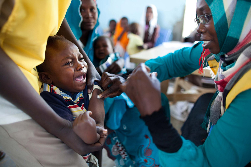 A child receives a vaccination against meningitis at the community centre in Al Neem camp for Internally Displaced People in El Daein, East Darfur, Sudan. Photo: UNAMID/Albert González Farran