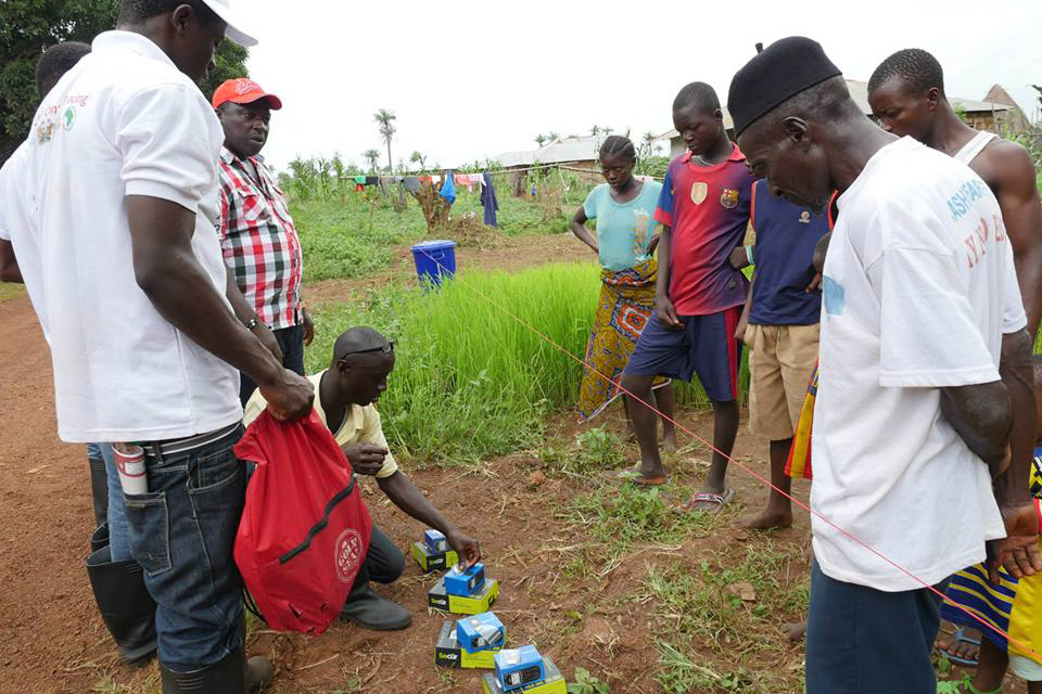 Mobile phones with solar-powered chargers are distributed to all Ebola-quarantined homes in Sella Kafta, Sierra Leone, allowing them to stay in touch with friends and family, which lessens anxiety and resentment.