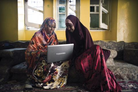 Two students from Mogadishu University using a laptop for their studies
