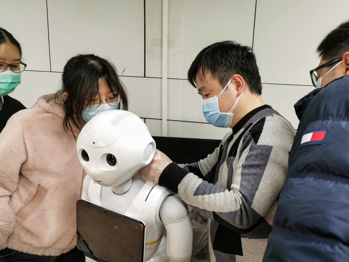 Individuals wearing protective gear working on robot