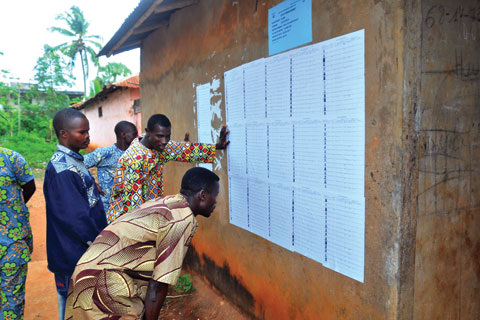 Voters look for their names on voter registration lists outside a polling station in Benin