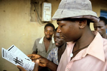 African man reading an AIDS education pamphlet in Uganda