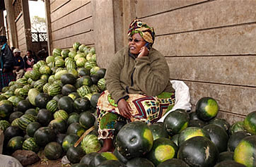 A seller of melons using her mobile phone at a fruit and vegetable market in Nairobi, Kenya
