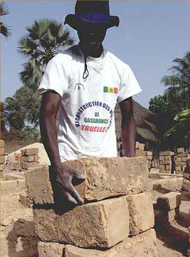 Young volunteer helping rebuild a Casamance village destroyed in the war