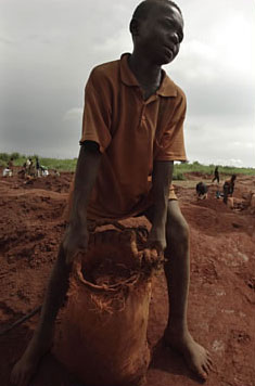 A 13-year-old boy carries a sack of earth and rock at a diamond mine