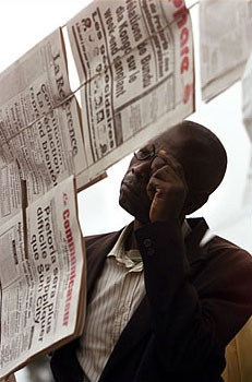 Man reading a newspaper in Kinshasa