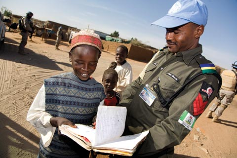 UNAMID officer looks over a student's school work at a North Darfur camp for displaced people