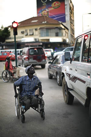 Beggar in wheelchair approaching a car.