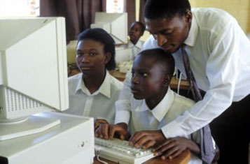 Teacher showing secondary students how to use computers