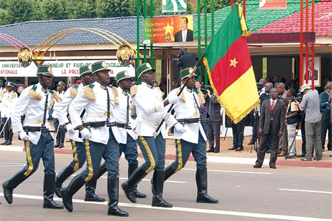 Showing the flag at the Independence Day march in Cameroon: President Paul Biya and other leaders note, however, that most African countries remain highly dependent on an international economy over which they have little influence.