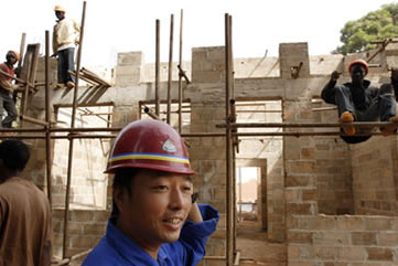 A Chinese foreman walks past a construction site in Guinea-Bissau