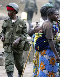 Soldiers walking near two mothers with young children