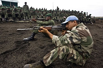 A UN peacekeeper instructs Congolese troops