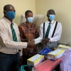 Dr. Mamadu Baldeh (center) receiving Personal Protective Equipments (PPEs)