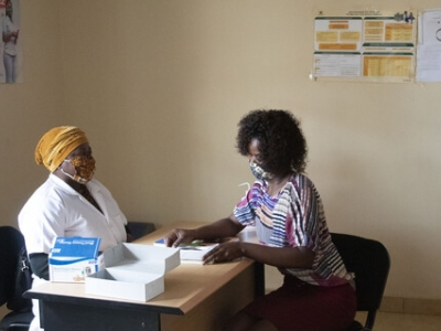 Carmen Omar, a social worker and coordinator at the Nampula one-stop centre, speaks with a maternal and child health nurse in the health department room, where survivors are assessed and receive medical treatment. UNFPA / Roberto Manjate