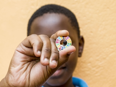 A student holding an SDG badge. Photo: Solomon Musisi