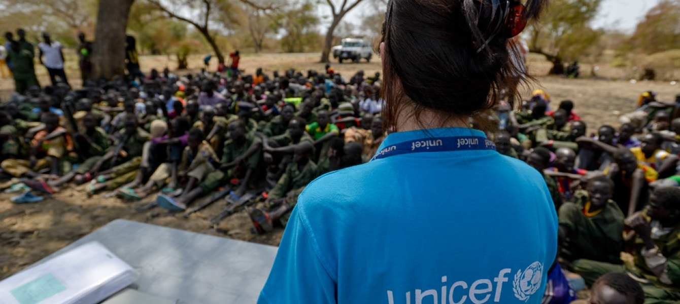 A UNICEF worker stands in front of a group of children undergoing release from the SSDA Cobra Faction armed group, in Pibor, Jonglei State on 10 February 2015. Photo: UNICEF/Sebastian Rich