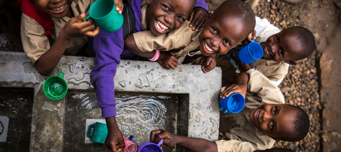Children fill their cups at a water point built by UNICEF at Kanyosha III primary school in Bujumbura, Burundi. Photo: UNICEF/Rosalie Colfs