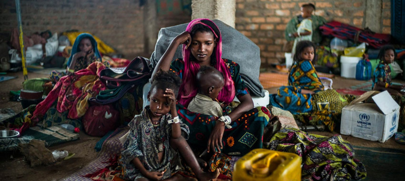Hajara, 19, and her children await their first hot meal in over two months. They arrived in Dosseye refugee camp the previous day after fleeing violence in Central African Republic. UNHCR/C.Fohlen