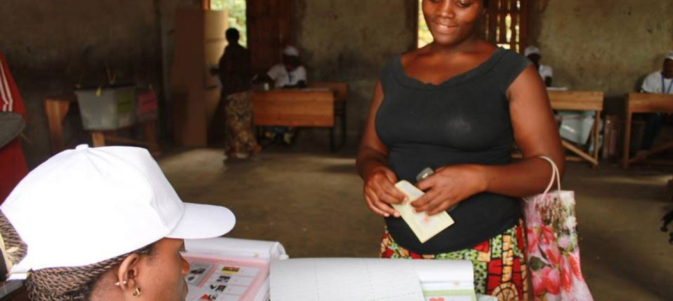 An electoral worker checks names against the voters' list at a polling station during elections in Burundi. Photo: MENUB