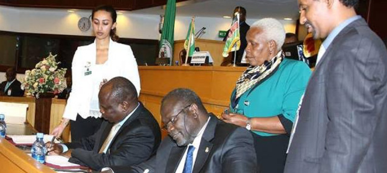 Former South Sudan Vice President Riek Machar (seated right) and Pagan Amum Okiech, representing the Former Detainees, sign the compromise peace agreement put forth by the Intergovernmental Authority on Development Partners Forum (IGAD) mediation in Addis