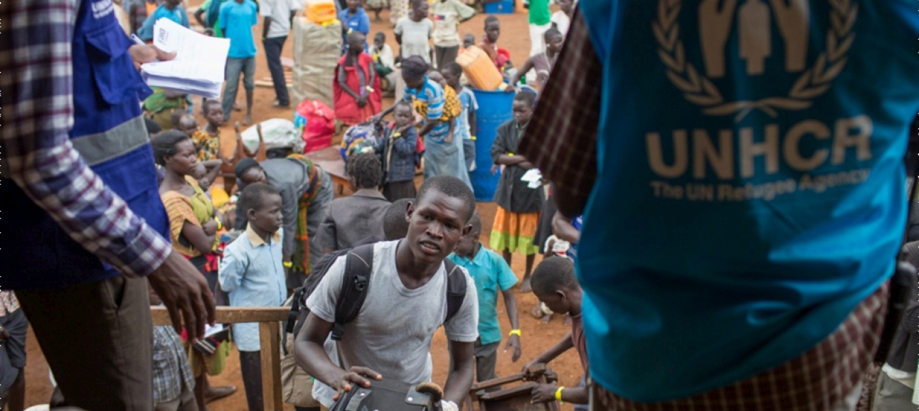 A recently arrived South Sudanese refugee loads his belongings into a UNHCR truck at the South Sudan border with Uganda. Photo: UNHCR/Will Swanson