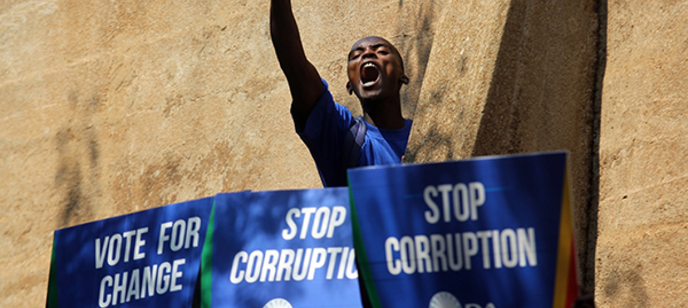 A protester outside the Constitutional Court in Johannesburg, South Africa. Photo: AP Photo/Denis Farrell