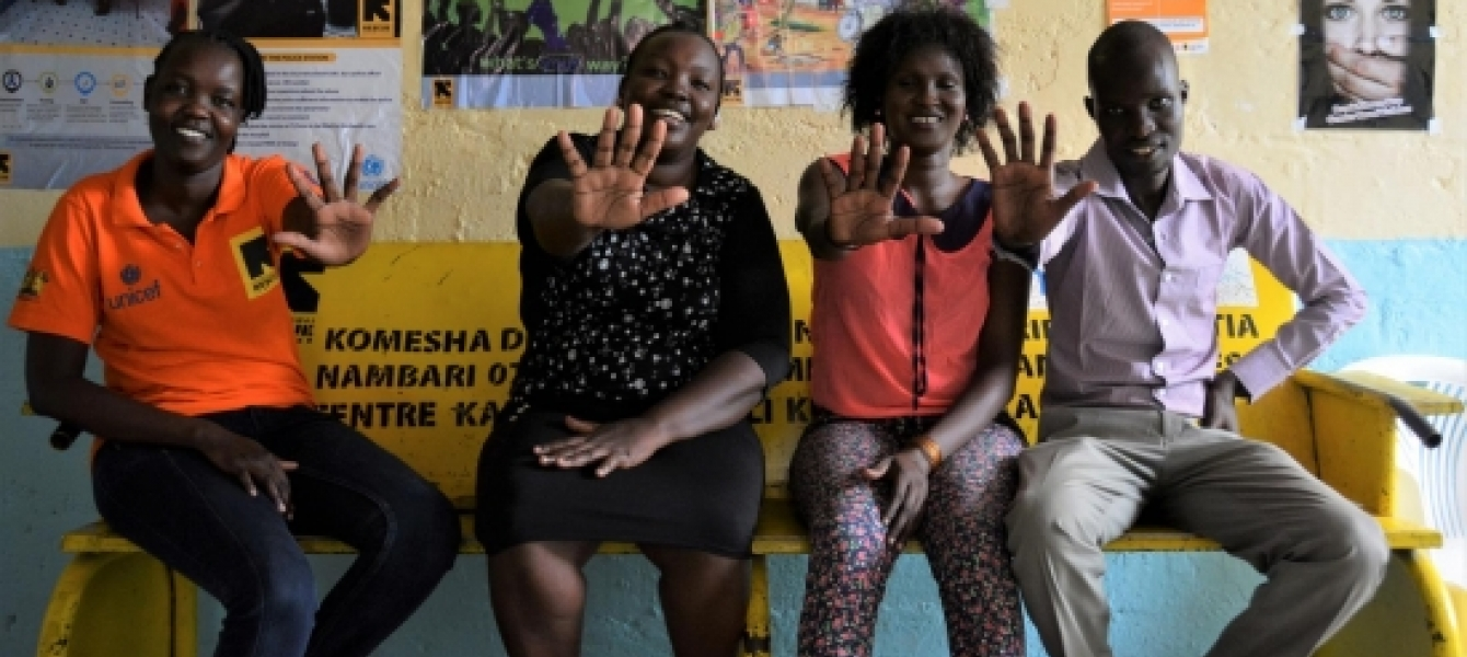 Staff at the Lodwar Hospital Wellness Centre make a 'stop violence against children' hand sign in February 2020 (before the outbreak of COVID-19 in Kenya). The centre supports child survivors of violence and abuse.
