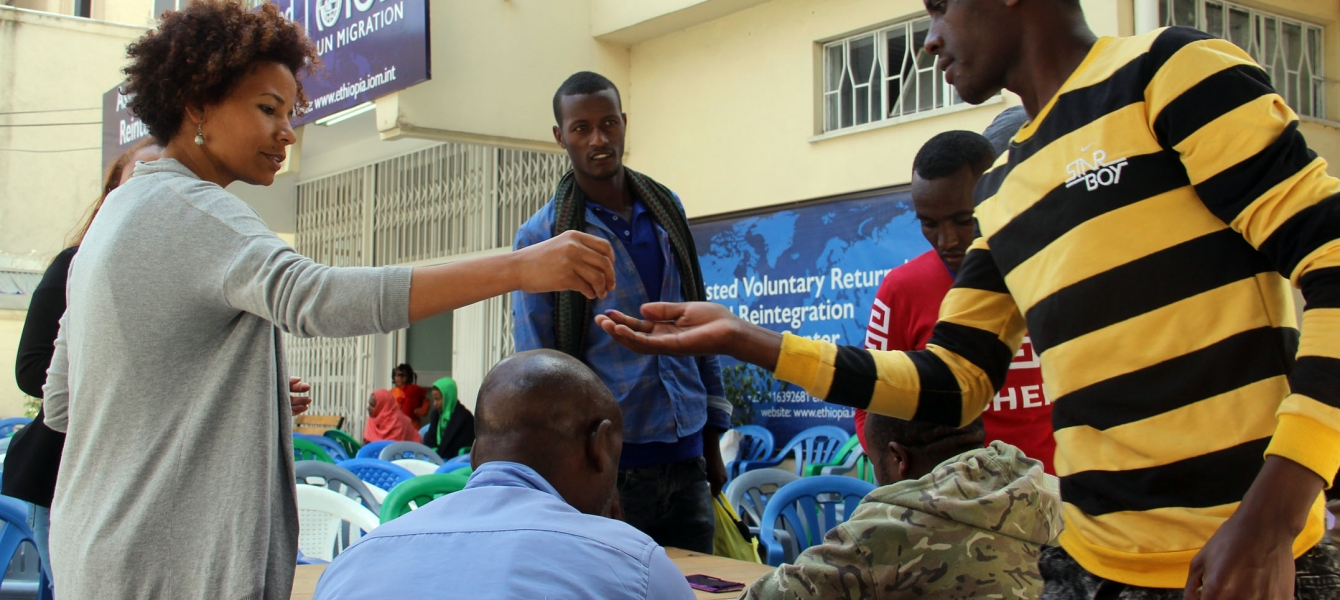 Ethiopian migrants from Tanzania receive onward transportation allowance at IOM's Transit Centre in Addis Ababa.