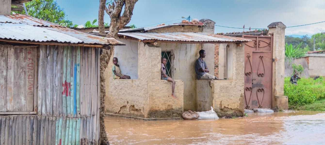 Children sit idly with their father, observing the destruction of their community's homes in Bujumbura Rural Province, Burundi.
