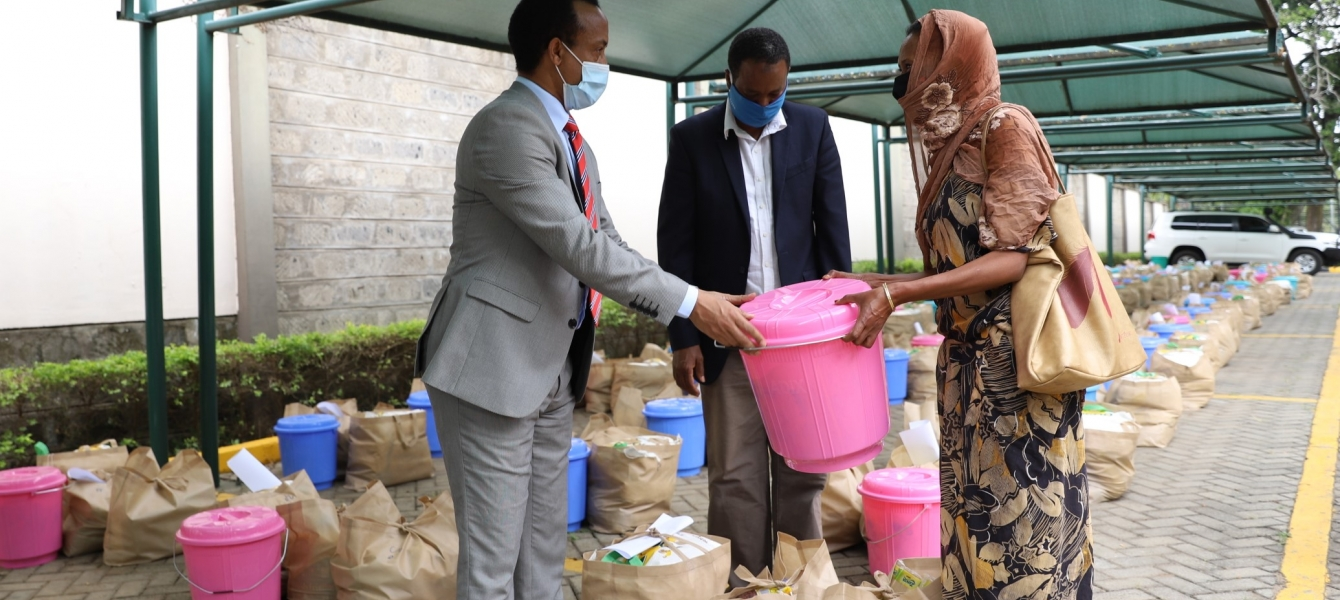 Meles Alem, Ethiopian Ambassador to Kenya handing over food donation to one of the beneficiaries.