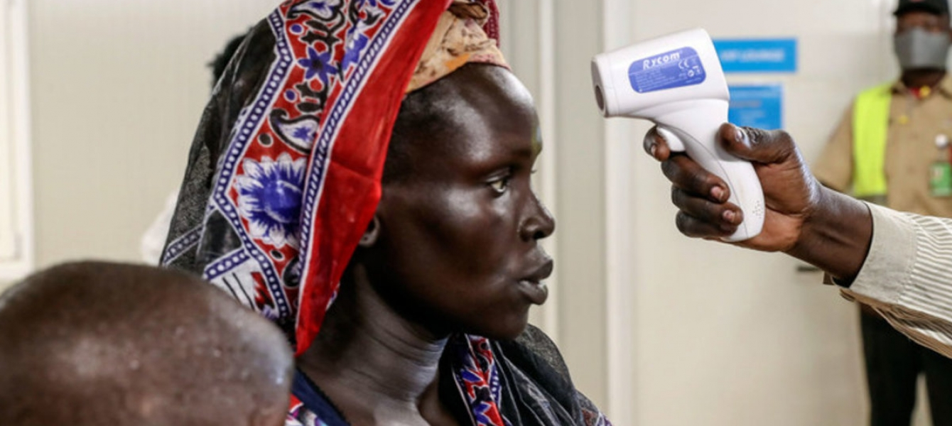An internally displaced woman voluntarily returning to her home in Bentiu, South Sudan, is being checked for fever.