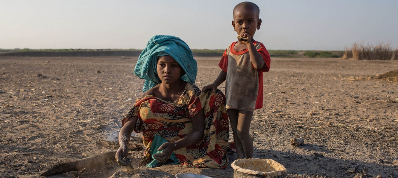 A young girl cooks in a rural village in Ethiopia, where the land has been affected by recurrent droughts.