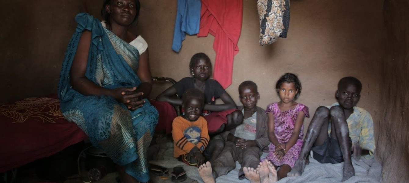 Mary Amaik and her family sit in their small house in Pibor, South Sudan.