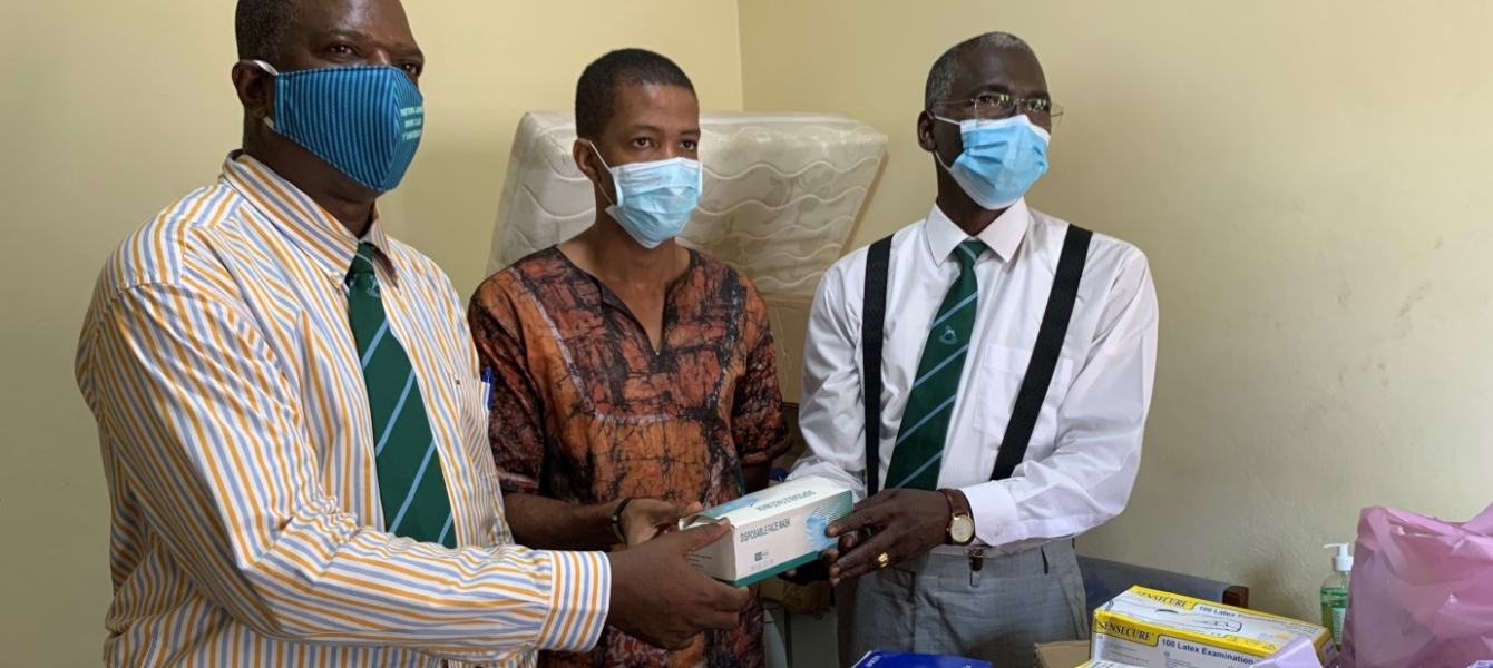 Dr. Mamadu Baldeh (center)received donated Personal Protective Equipments (PPE)