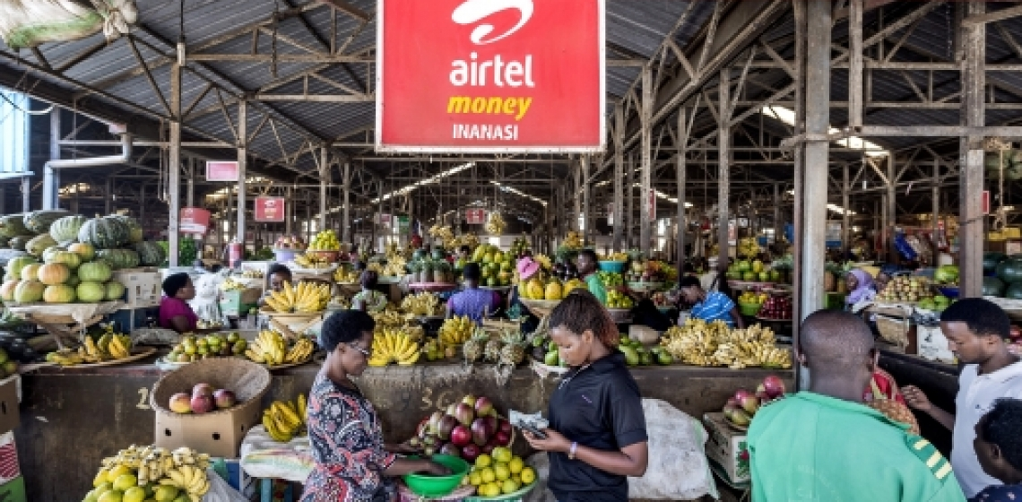 An advertisement for a mobile phone money transfer company hangs over stalls of fruit and vegetables at a covered market in Kigali, Rwanda. Photo: Panos/Sven Torfinn
