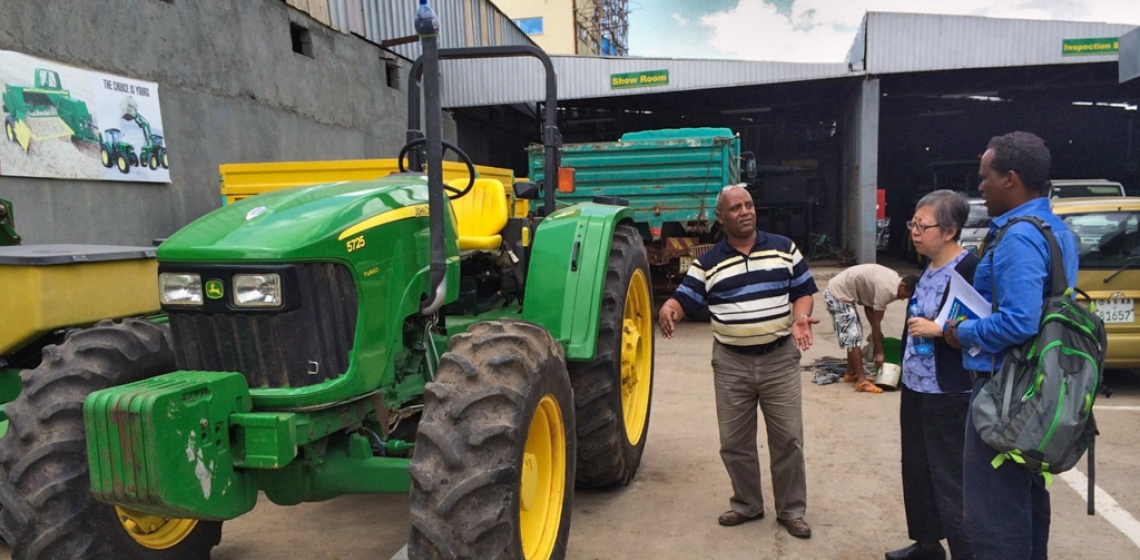 Factory worker in Ethiopia explaining tractor use to colleagues.