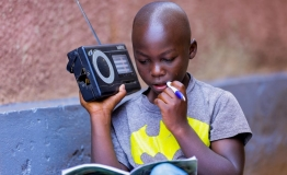 Igihozo, 11, listens to a lesson on a radio after his school was closed in Rwanda.