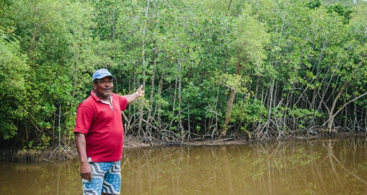"Seychellois farmer, Pierre Philoe, explains how mangroves protect his farm from intruding seawater that kills his crops. ""The mangroves are important for all Seychellois people. If there's no mangrove, there's no life."" Photo by UN Environment Programme /"
