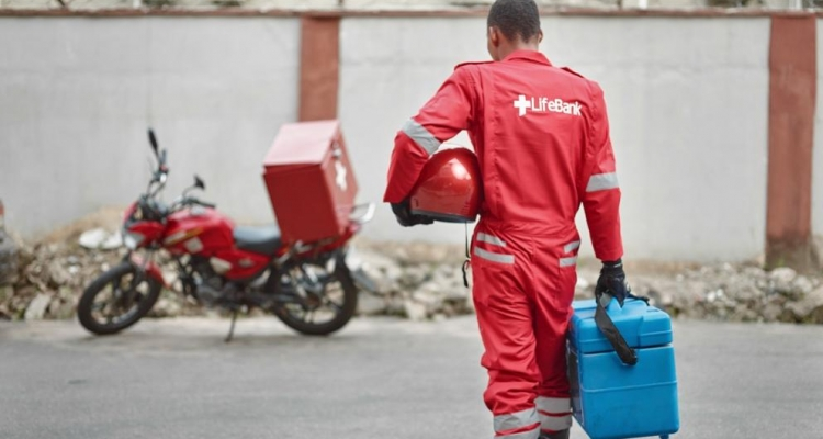 A LifeBank Dispatch Rider walking towards his motorbike with one of our WHO Blood Safety Compliant Cold Chain Blood Boxes.