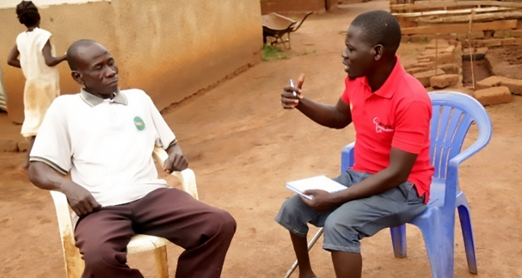 Home Health Promoter Eliaba Anthony Amba (right) speaks with Bennet Khamis.