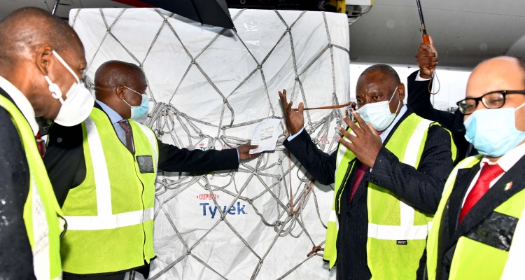an image of President Cyril Ramaphosa (third) receiving South Africa's first consignment of COVID-19 vaccine from the Serum Institute of India (SII) at the Oliver Reginald Tambo International Airport in Johannesburg.