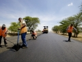 Workers take measurements while laying the tarmac on a new road being built near Arusha, Tanzania. Africa needs funds for such development projects. Panos/Frederic Courbet