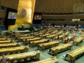 A wide view of the General Assembly Hall as Raffi Gregorian (at dais and on screens)...