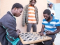 Migrants play a board game at IOM Transit Center in Agadez, Niger (2016).