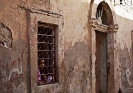 A girl looks out of her house window in Benghazi, Libya. Photo: UNSMIL