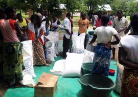 People gather at Mikolongo school in Chikwawa district, Malawi, to receive rations of maize, pulses, oil and fortified corn soya blend from WFP to prevent malnutrition. Photo: WFP/Dannie Phiri