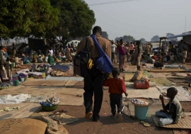 A man and his child walk through a crowded site for internally displaced people in the Central African Republic capital, Bangui, where many people remain at risk. Photo: UNHCR/S. Phelps