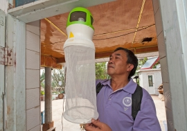 Health worker checking the installation of an anti-mosquito device at the entrance of a house. Such devices may help to trap mosquitoes, flies and insects. Photo: WHO/TDR/S. Lim